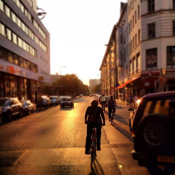 She's on a mission. Berlin by bicycle, half-summer light.