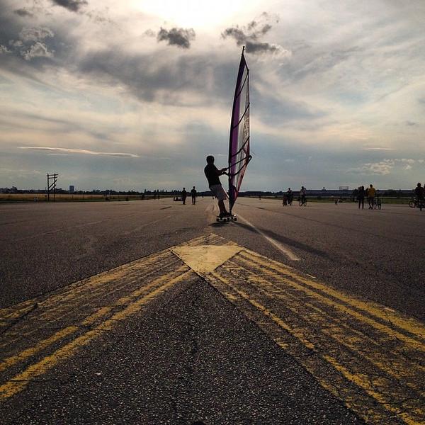 A kitesurfer carves up the main runway at Berlin Tempelhofer Freiheit.