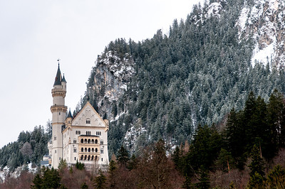 The Neuschwanstein Castle against a snowy hill in Germany