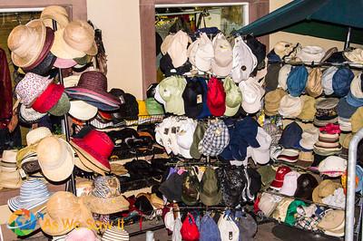 A comical variety of hats along an open street market.