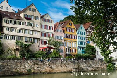 People sitting on the wall by the Neckar River in Tübingen, Germany