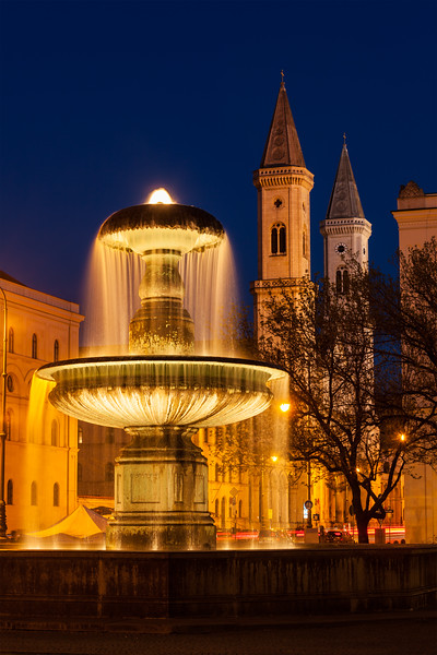 Fountain in the Geschwister-Scholl-Platz and St. Ludwig's Church (Ludwigskirche) in the evening. Munich, Bavaria, Germany