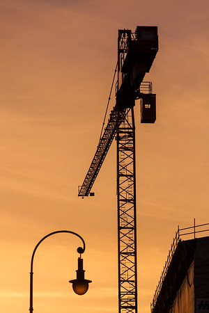 Building crane silhouettes in sky