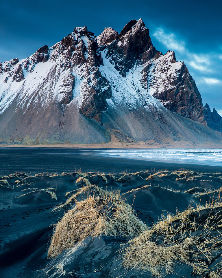 The dramatic contrast of the peaks and the black sand beaches