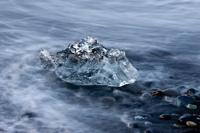 "An ""ice fish"" sits on the rocks as it slowly melts into the sea."