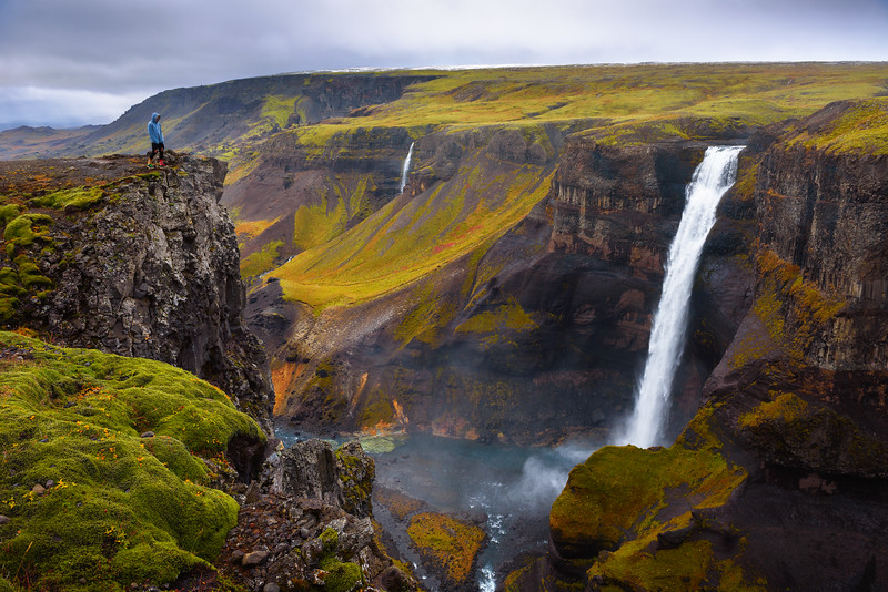 Hiker standing at the edge of the Haifoss waterfall in Iceland