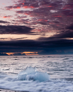 Pink clouds at sunrise as the surf washes over another chunk of glacial ice melting