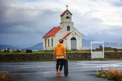 Young man with a skateboard looking at a church with a cemetery in Iceland