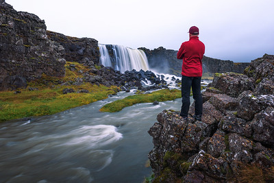 Tourist looking at the Oxarafoss waterfall in Iceland