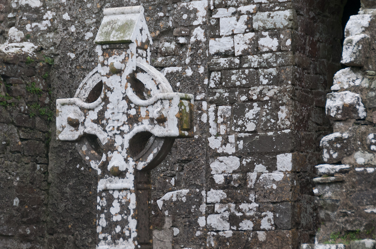 Close-up of cross and ruins at a burial grave site in Ireland