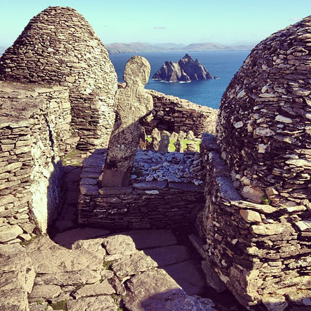 "Atop Skellig Michael, a 6th century monastic settlement on a rock island off the coast of Portmagee, County Kerry. Ancient burial cross and ""Small Skellig"" bird sanctuary island in the background. Absolutely remarkable spot, crystal weather to boot. #dna2"
