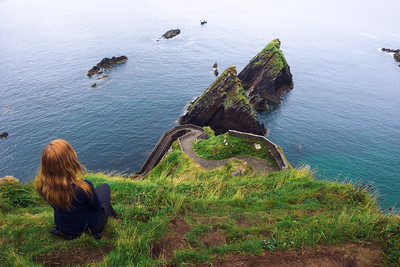 Girl sits on a cliff over the ocean in Ireland