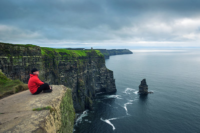 Hiker sitting at the cliffs of Moher