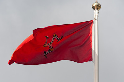 Close-up shot of the Isle of Man national flag waving on a pole