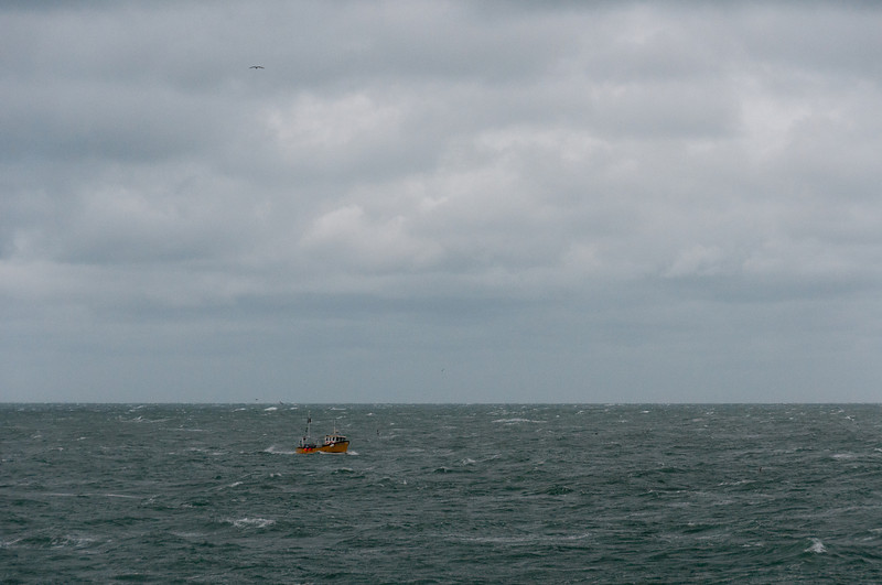 Solitary boat cruising the sea admist large waves in Isle of Man