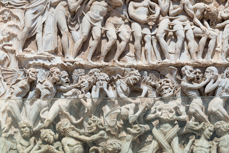 This is a close up of the lowest part of the wall sculpture from the picture previous to this one.  Made in 1350 A.D.<br /> Amazing detail and as you go up the wall the people are much happier and there aren't any demons lingering amongst them, eating there limbs, etc.