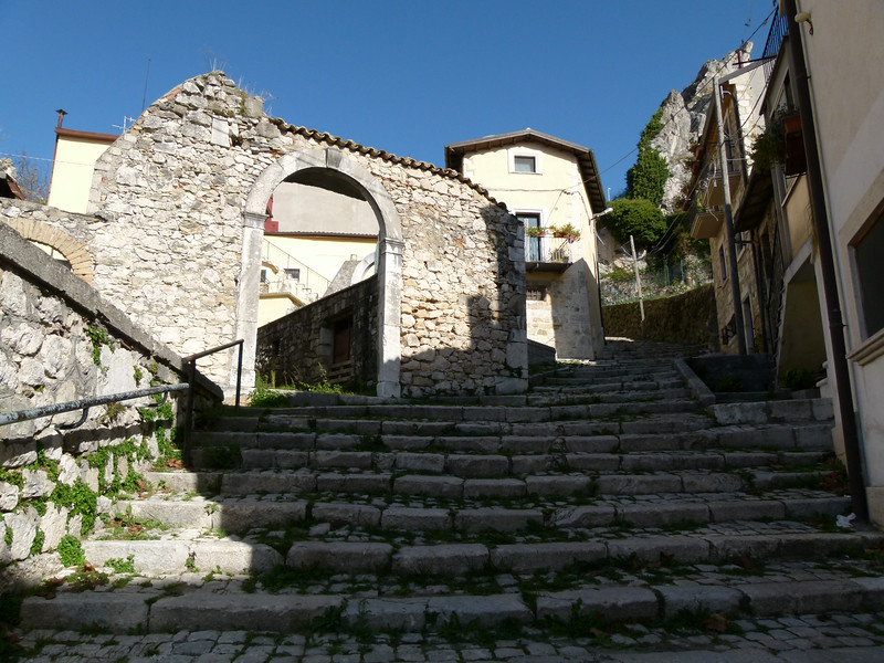 Wide stone steps lead up to a stone building with an arched entrance in Castel di Sangro.