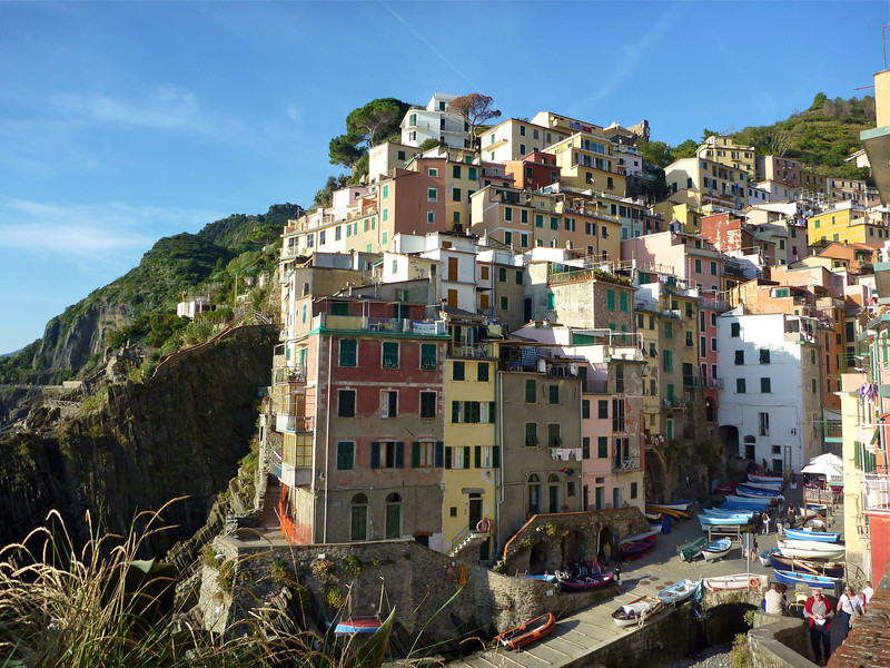 Pink, yellow and brown buildings tumble down the hillside at Riomaggiore, Cinque Terre.