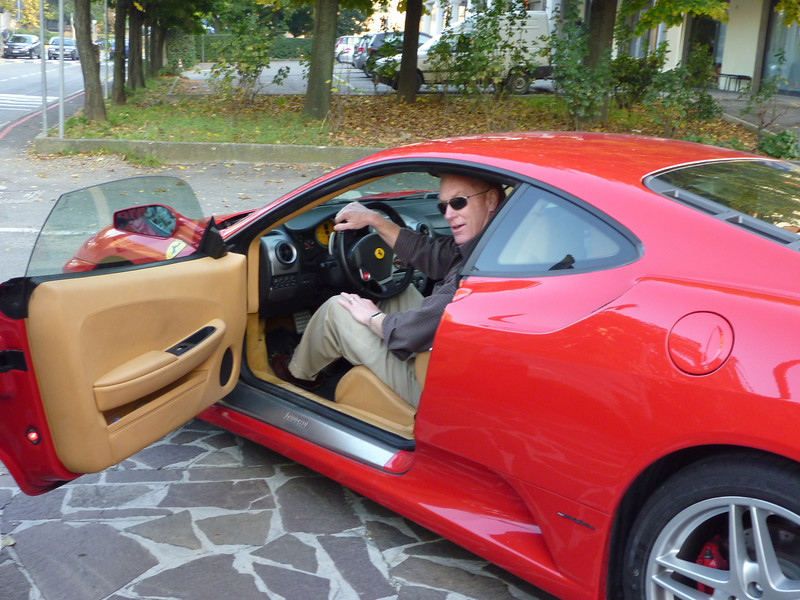 Man sitting in a red sports car with the door open