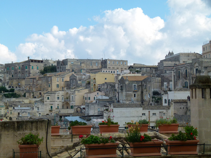 Stone houses of Matera crowd an Italian hillside.