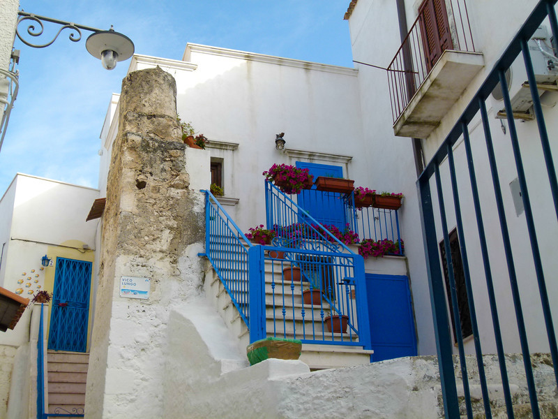 White buildings with blue wrought iron railings
