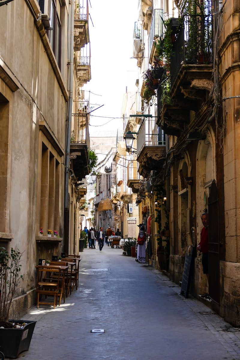 Cream colored buildings with wrought iron balconies crowd a narrow street on a Syracuse shore excursion in Sicily.