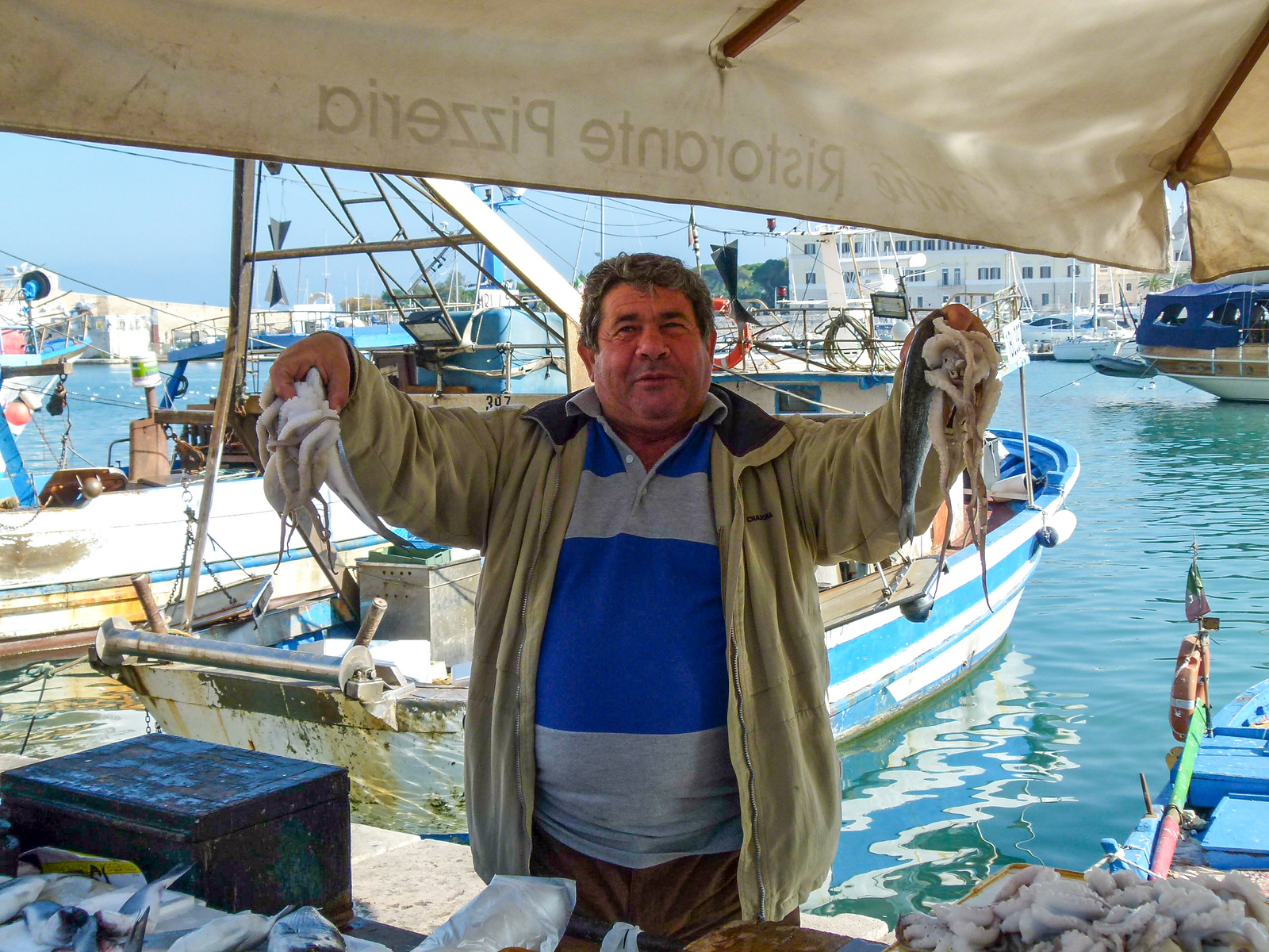 Selling seafood in the harbor of Trani, Italy. Include this seaside town on your boomer vacation in Italy. #Trani #Italy #vacation