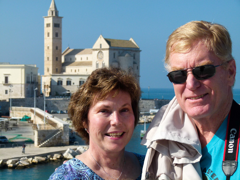Two boomers posing with the Trani cathedral in the background.