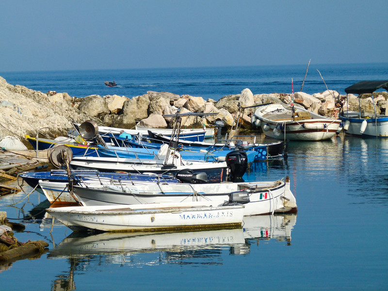 Small boats in a small harbor surrounded by rocks