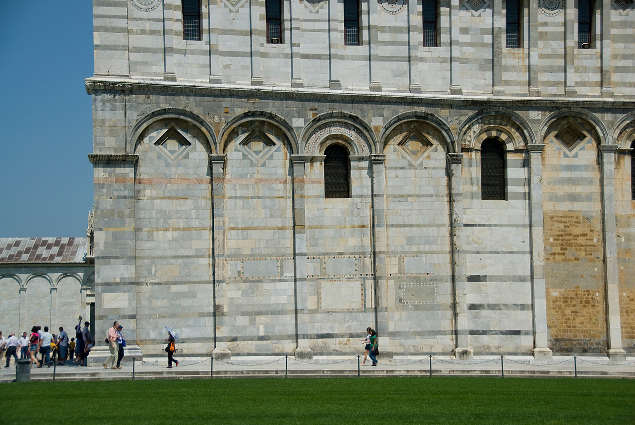 Tourists walking along the sides of Cathedral of Pisa - Italy