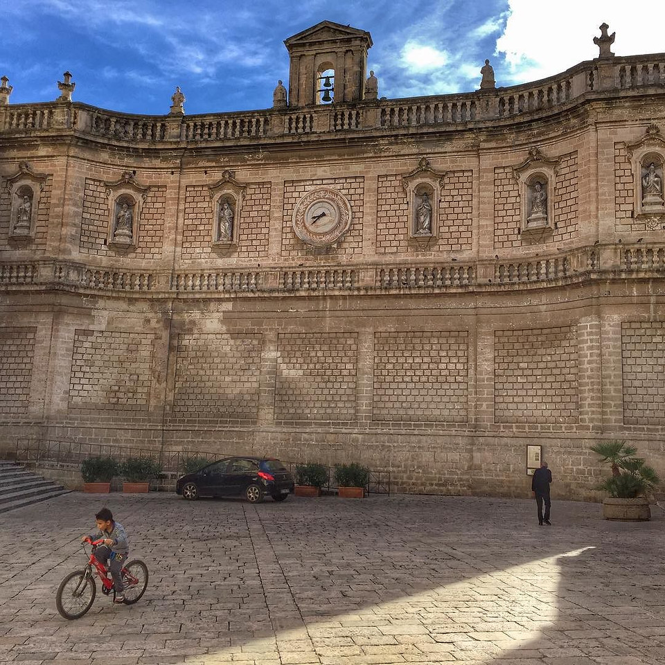 Every kid deserves a bicycle...and a bell tower -- Monopoli, Italy. A fleeting moment in front of the bell tower wall, Basilica Cattedrale di Maria Santissima della Madia (that's a mouthful, isn't it?). Another unscripted moment on our Puglia road trip. Details on where to find the little cyclist, on our blog (link in profile). via Instagram http://ift.tt/1YIWAPG