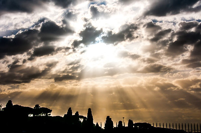 Sunlight streaking through clouds above Rome, Italy