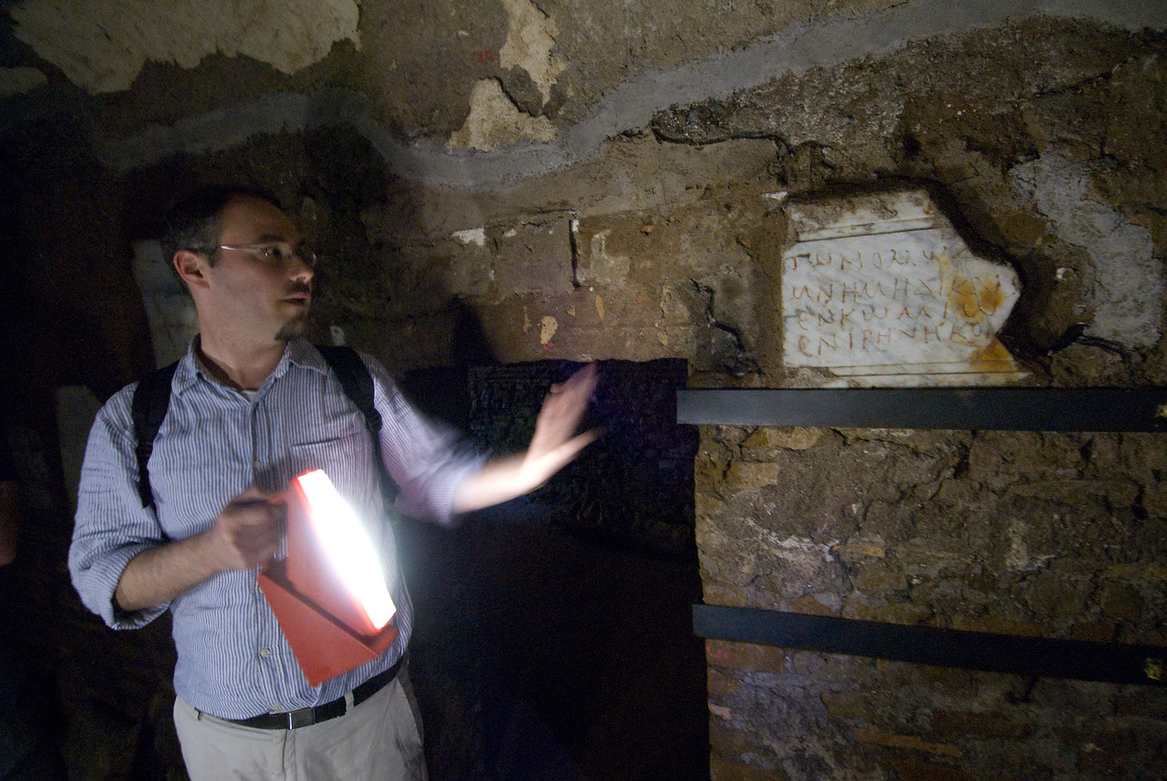 Tour guide showing history of archaeological site in Rome, Italy