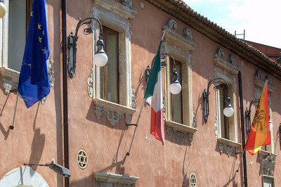 Flags hung on windows of a building in Sicily, Italy