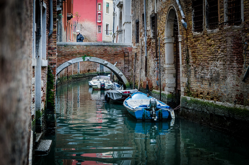 A woman crossing a bridge on a winter day in Venice.