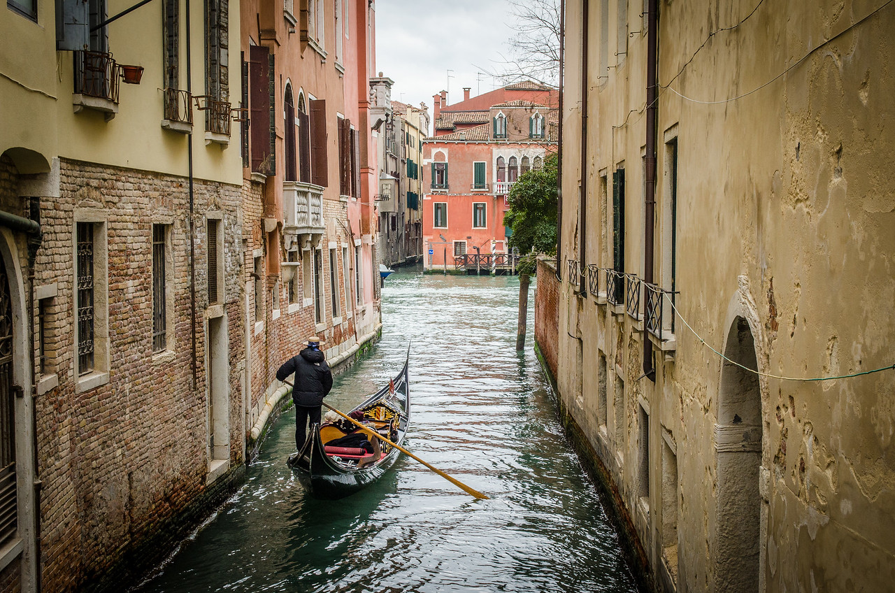 A gondolier with passengers on a winter day.