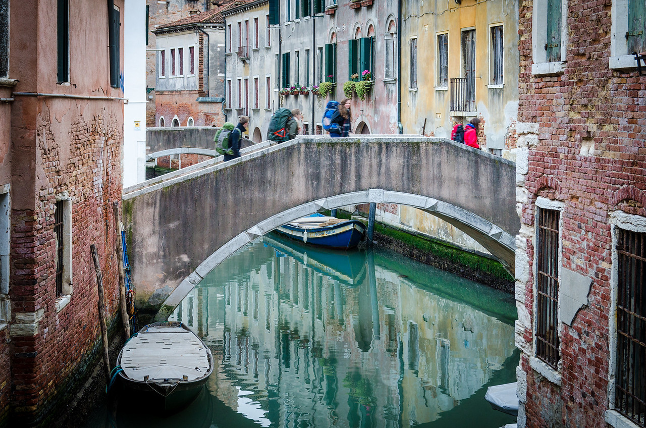 Backpackers crossing a bridge in Venice.