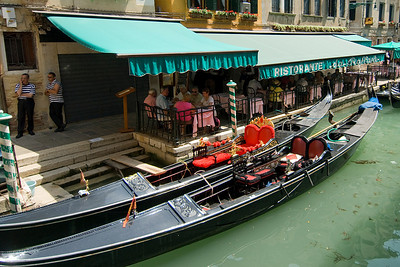 Empty gondolas parked next to a restaurant in Venice, Italy