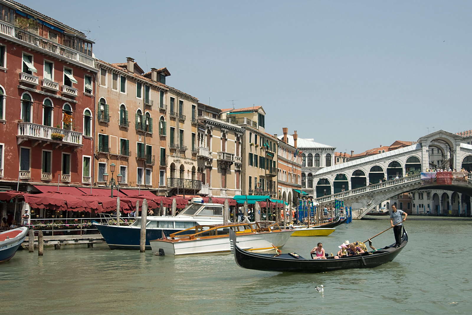 Tourists riding the gondola near Rialto Bridge in Venice, Italy