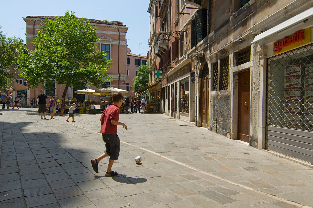 Kid playing soccer on the street of Venice, Italy