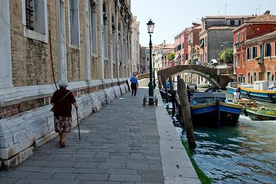 Pedestrian walk near parked gondolas in Venice, Italy