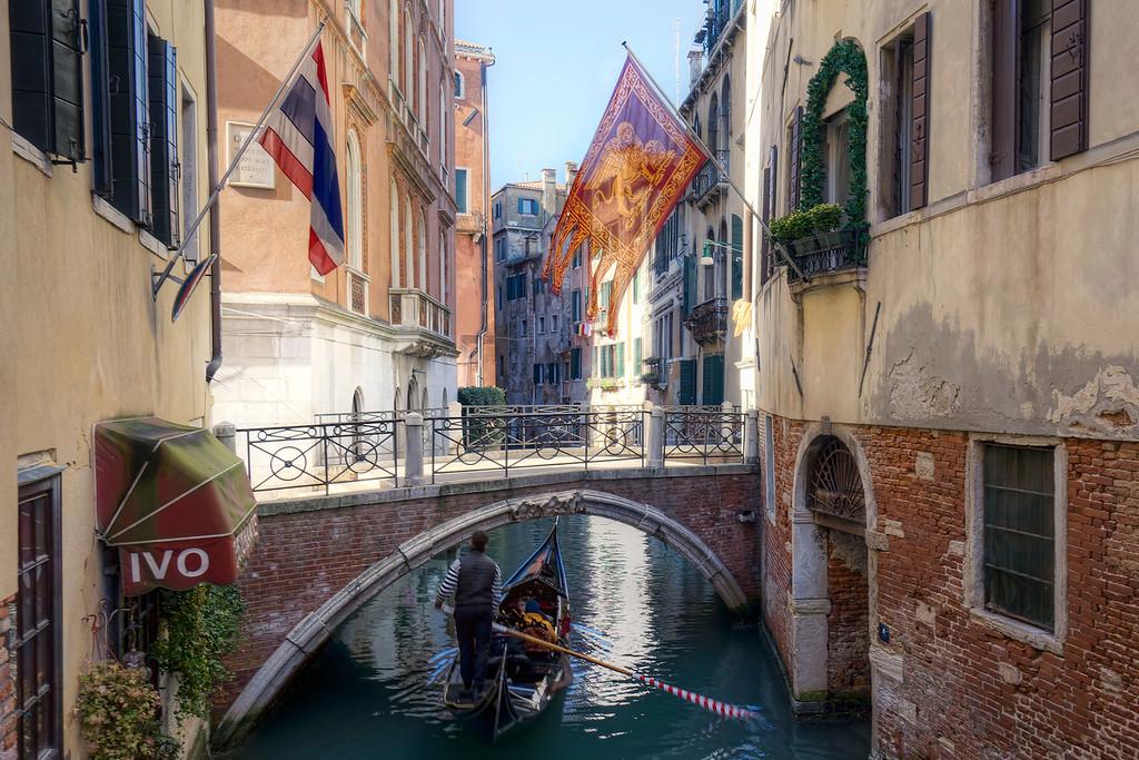 Gondola under bridge with lion flag above on a Venice canal.