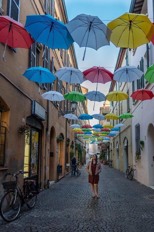 Amanda standing under colorful umbrellas in a street in Ravenna