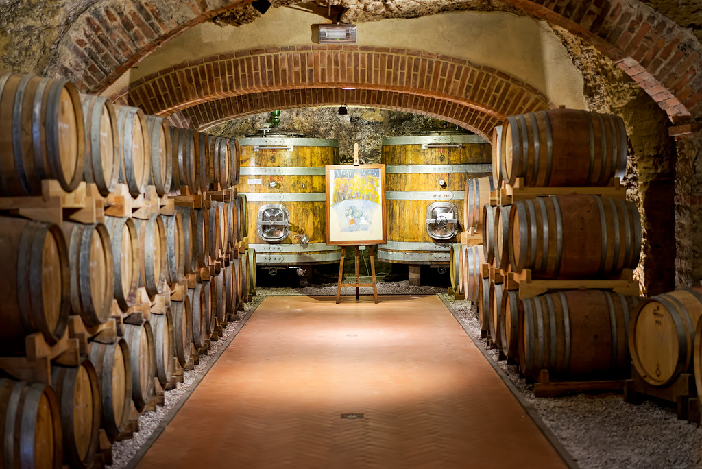 barrels of wine stored in a tuscan vineyards cave