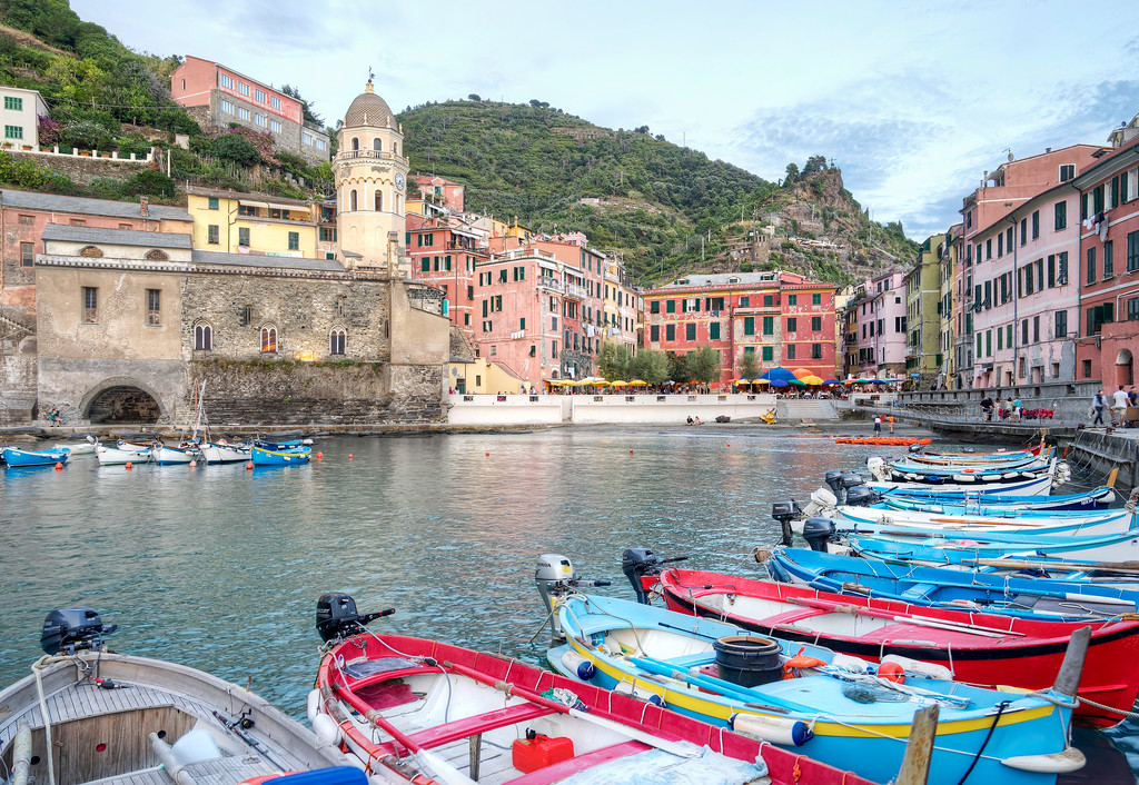 colourful small fishing boats in tiny harbour of vernazza with church and square in background cinque terre italy travel