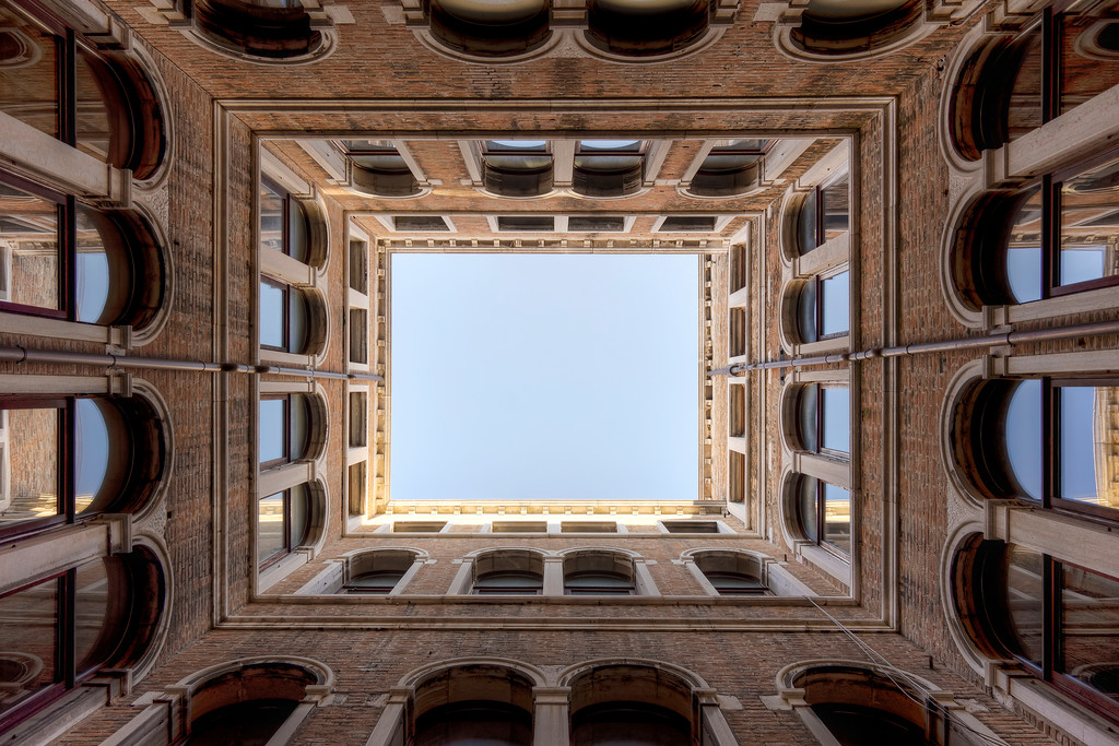 looking up at rectangular courtyard with glass windows and blue sky