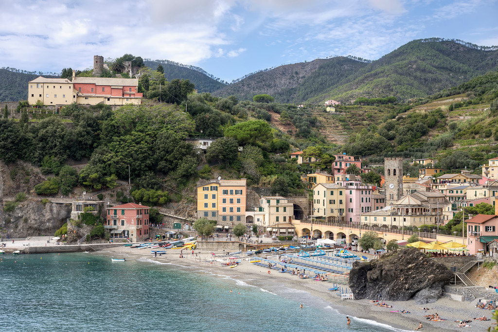 the beach at monterosso al mare with church and castle on hill and blue and wihte umbrellas and lounger chairs and bathers