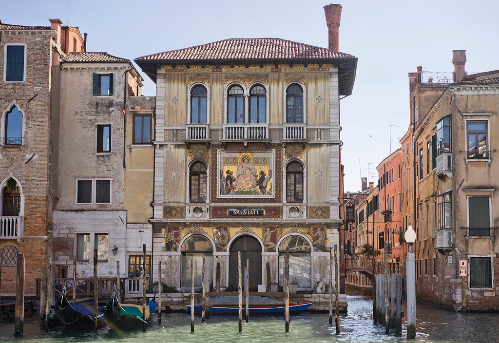 plazzo salviati facade with gondolas and view down canal with bridge and blue sky
