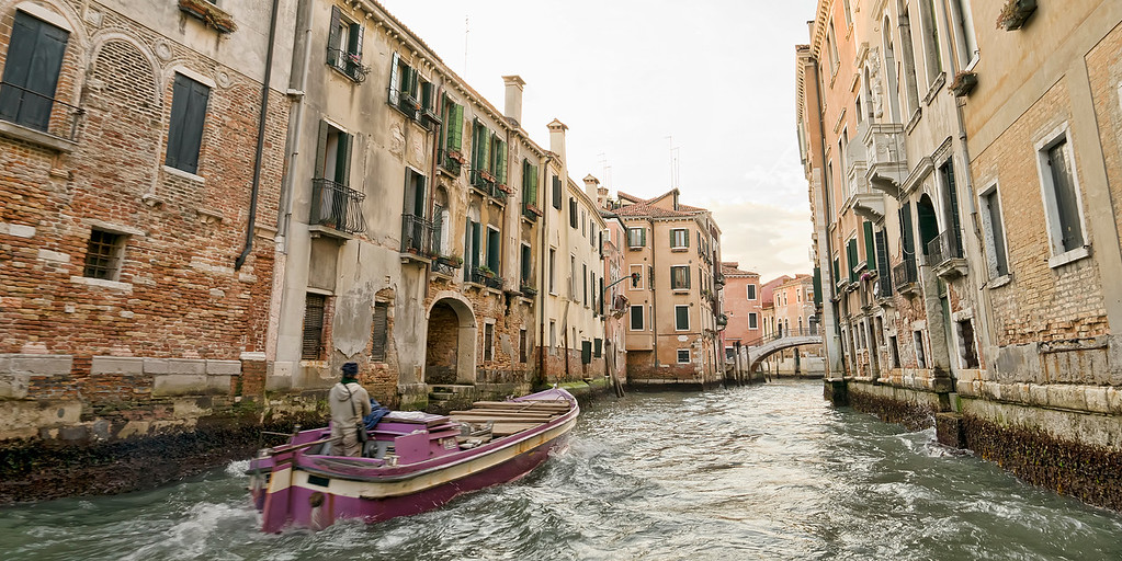 purple barge in rough water in venice canal with decaying buildings