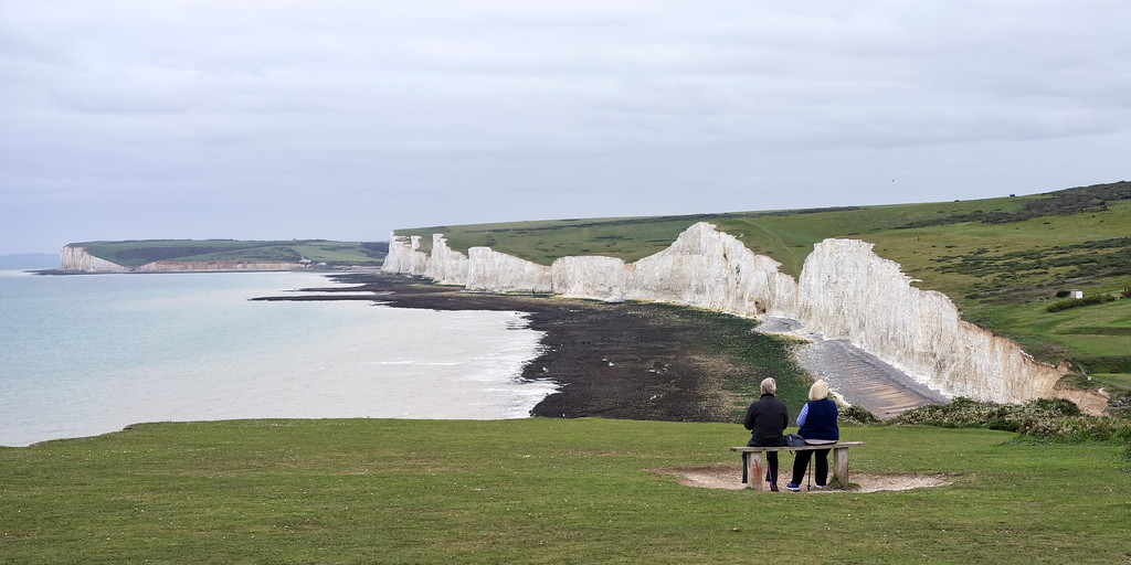 couple on bench viewing seven sisters cliffs south downs england